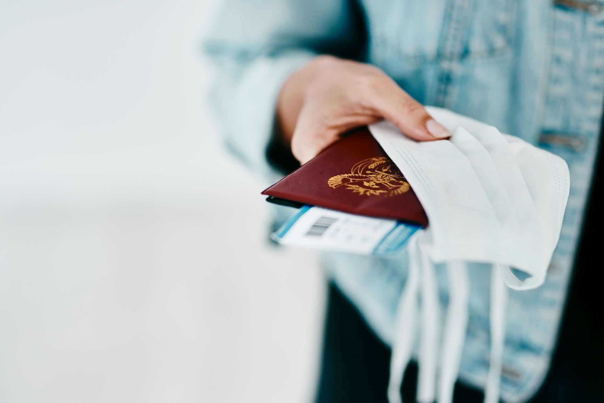 Frau hält Reisepass, Ticket und Maske in der Hand