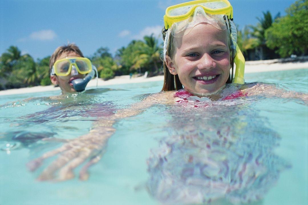 Junge und Mädchen mit Taucherbrille und Schnorchel im Pool