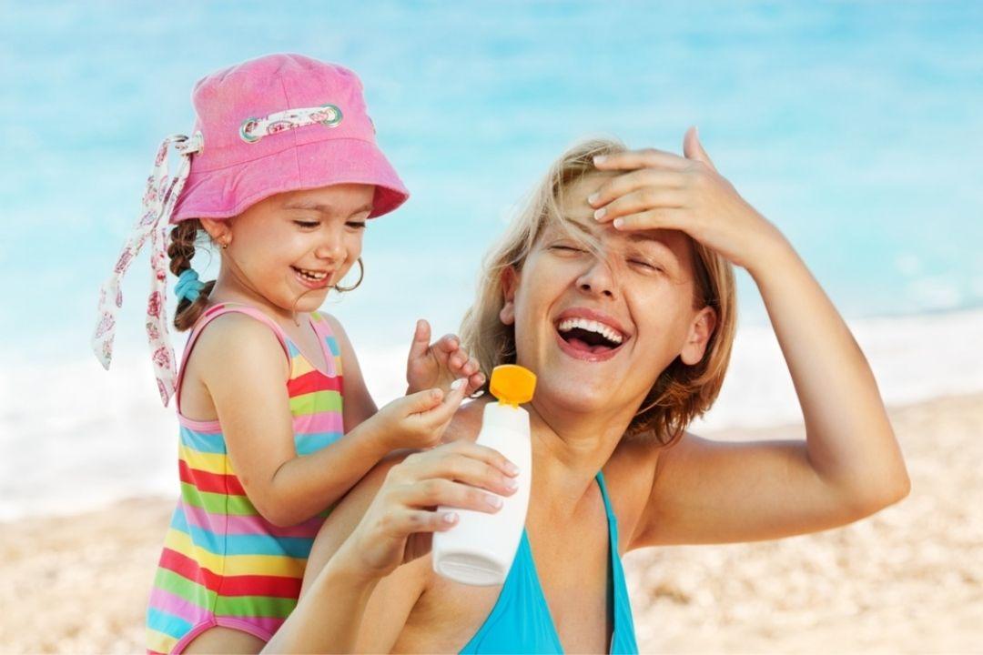 Kind schmiert Mutter mit Sonnencreme ein