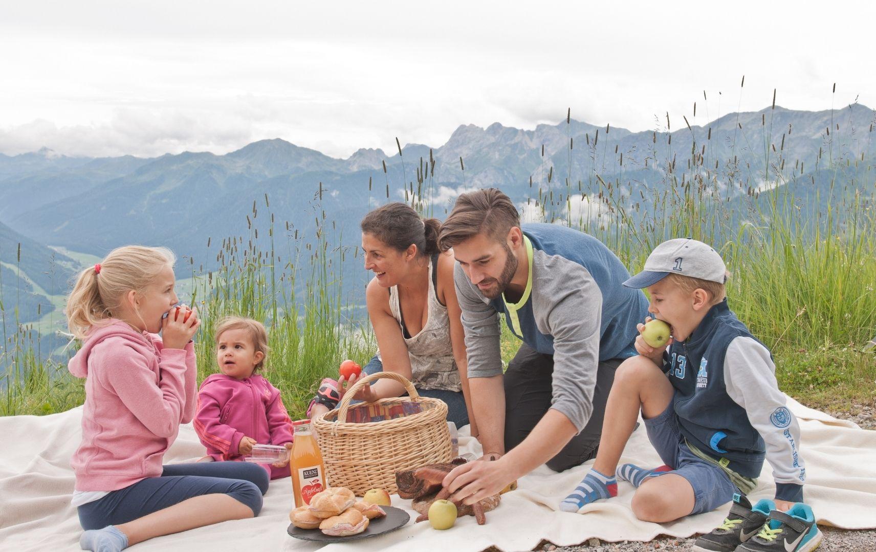 Familie sitzt auf Decke mit Picknick Korb