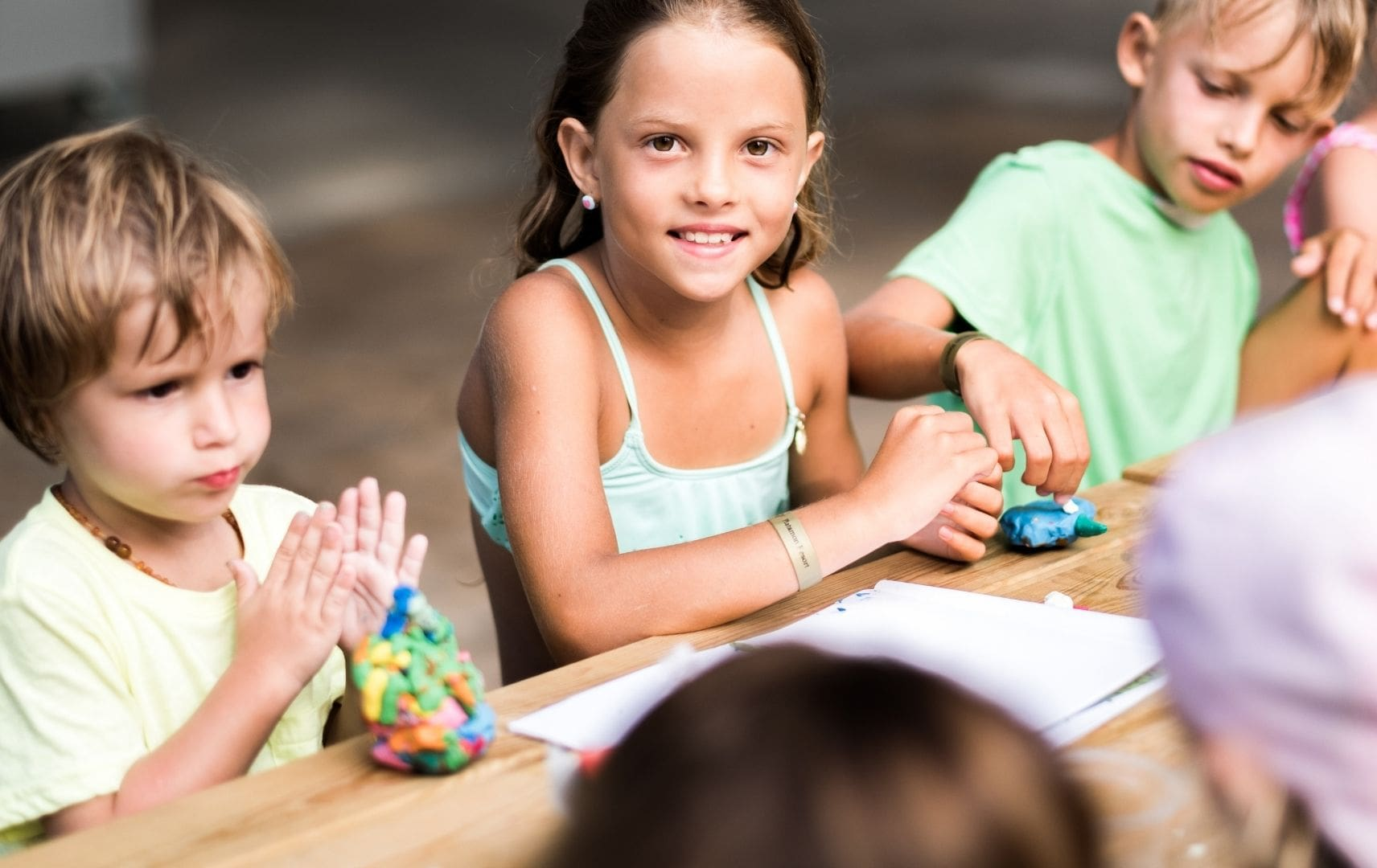 Ein Mädchen und zwei Jungs kneten am Tisch