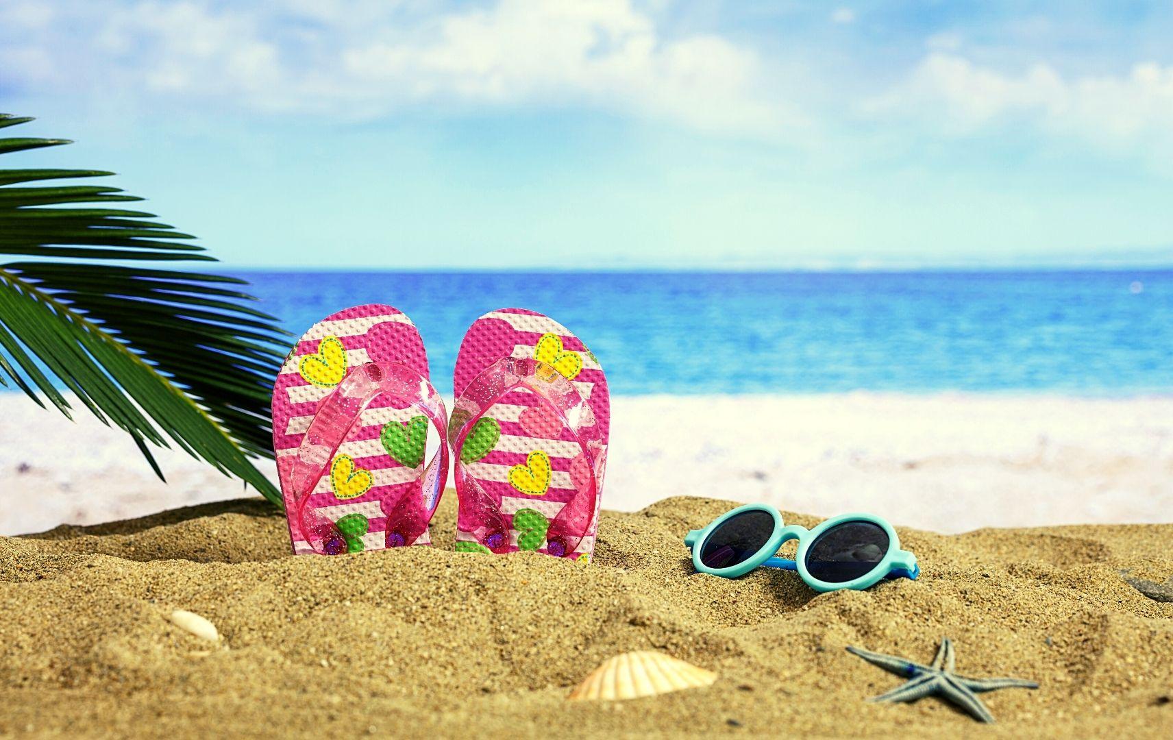 Kinder Flip Flops und Sonnenbrille im Sand