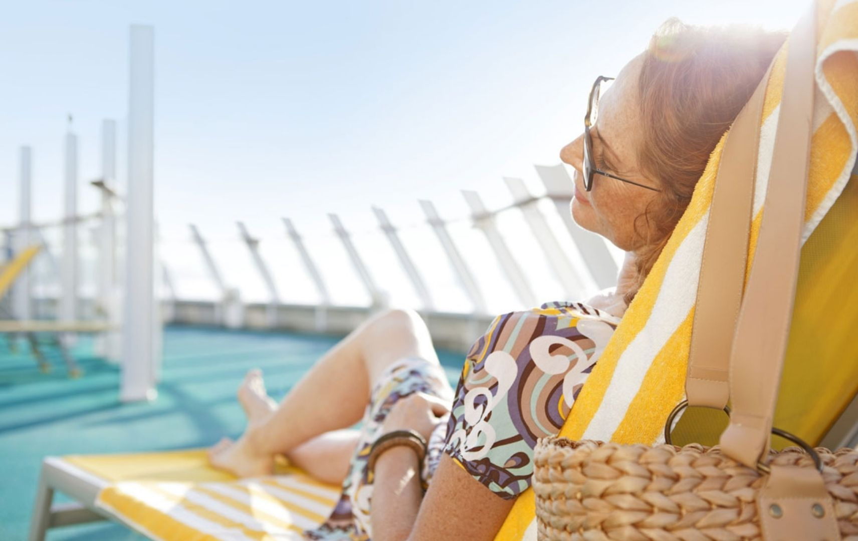 Frau liegt mit Sonnenbrille auf Liege auf Kreuzfahrtschiff Deck