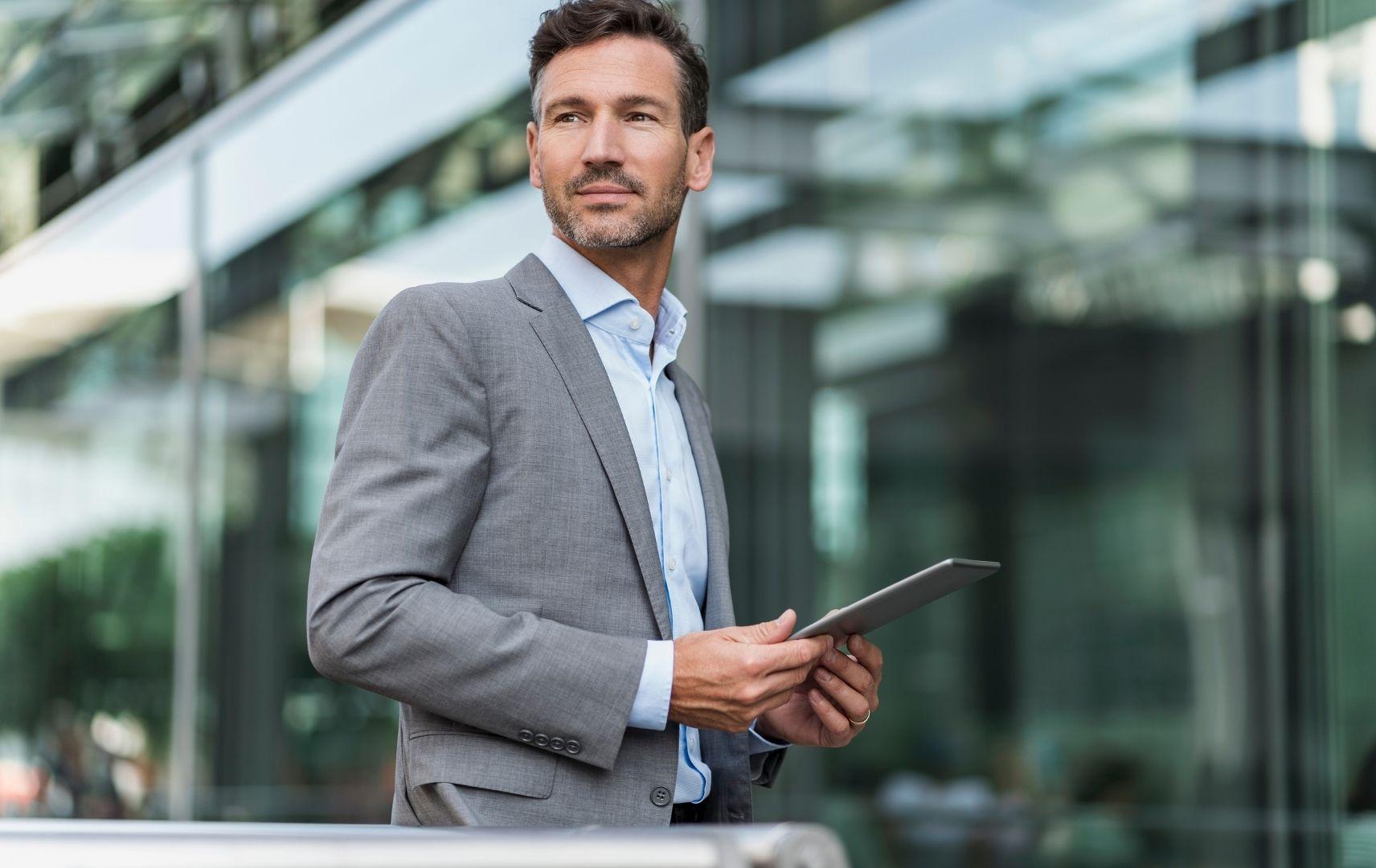 Businessmann mit Tablet vor Gebäude