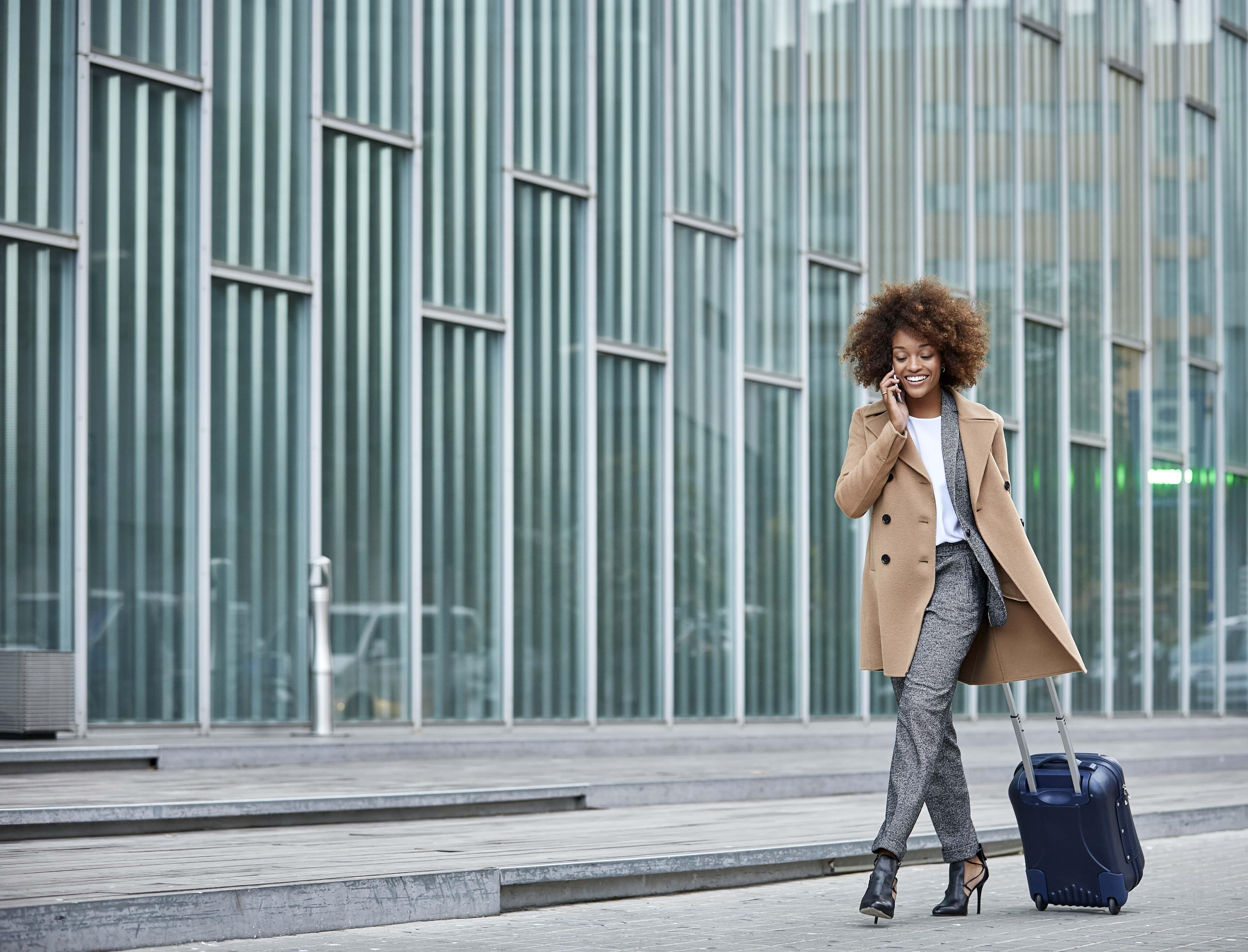 Geschäftsreisende mit Koffer und Smartphone