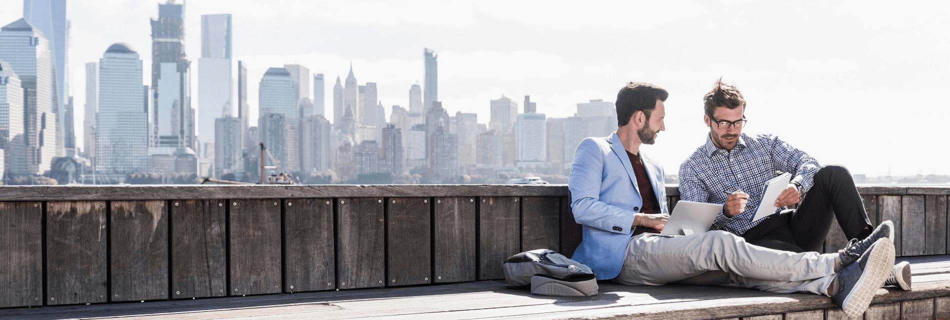 Herren unterhalten sich vor einer City-Skyline