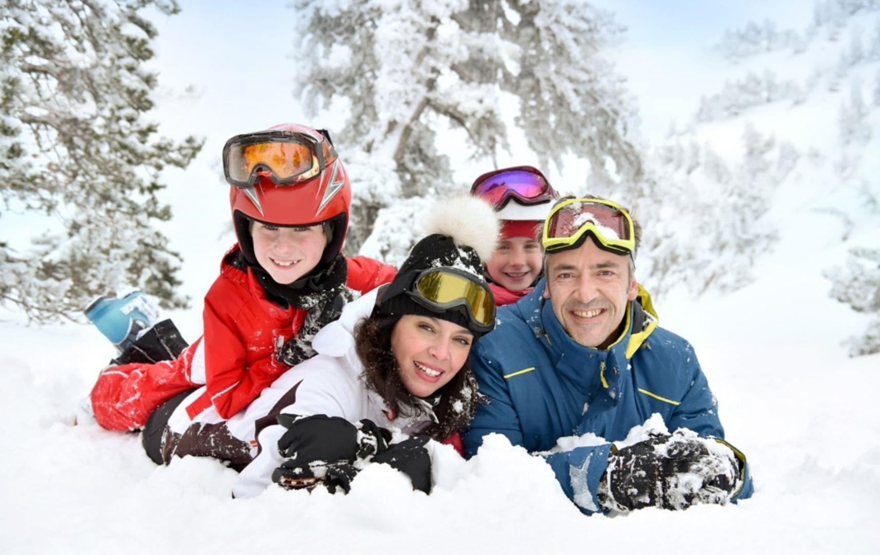 Mann Frau und Kinder liegen mit Schneeanzügen im Schnee
