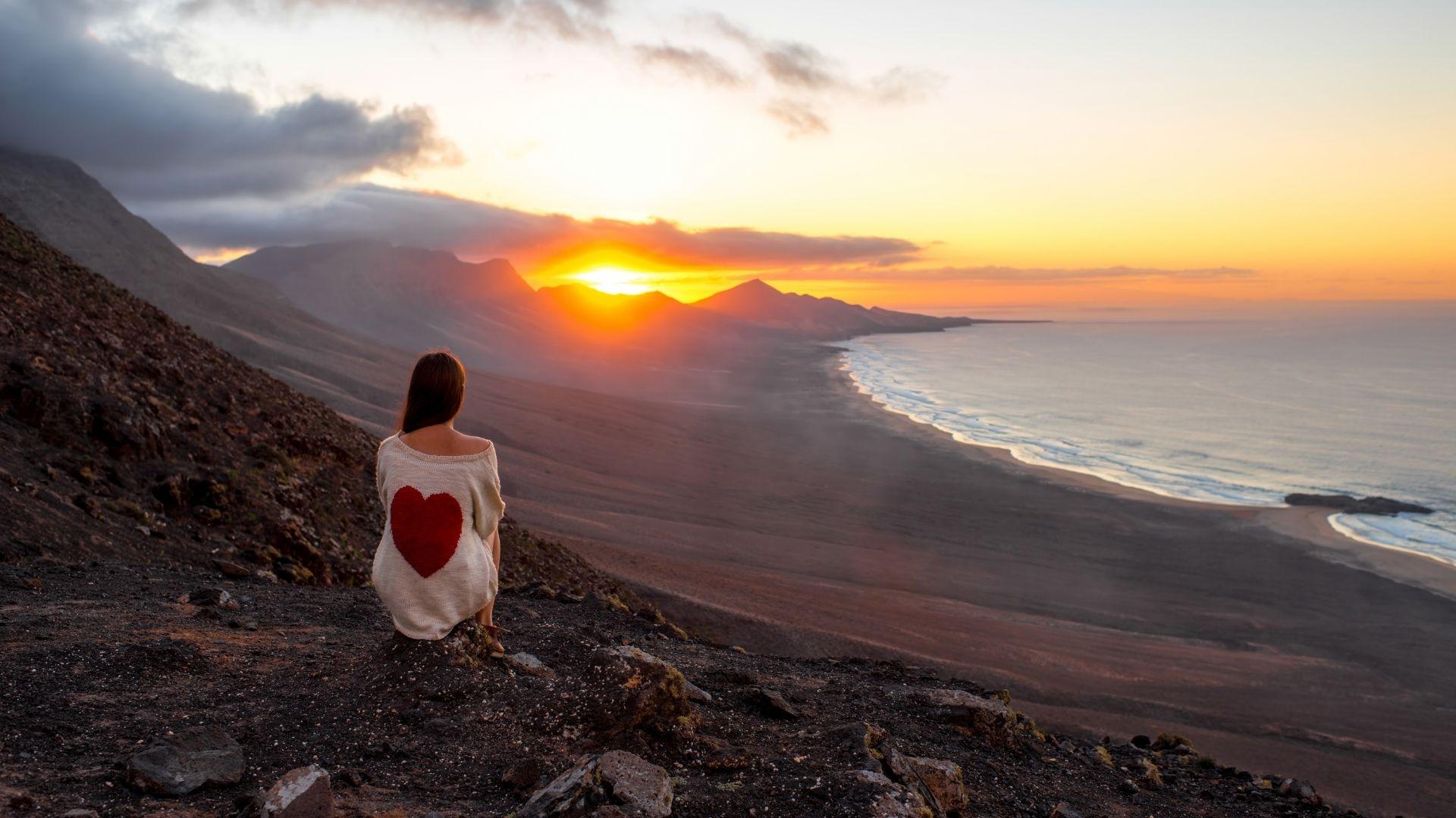 Frau sieht den Sonnenuntergang auf Fuerteventura