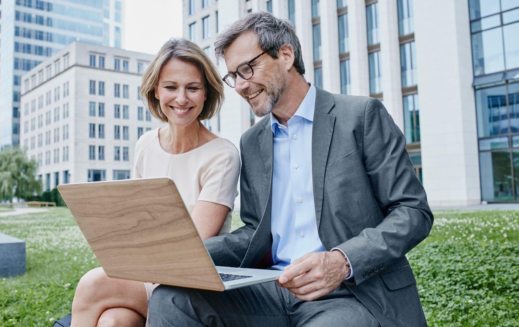 Geschäftsreiseservice rund um die Uhr Geschäftsmann und Geschäftsfrau mit Laptop in der Frankfurter City