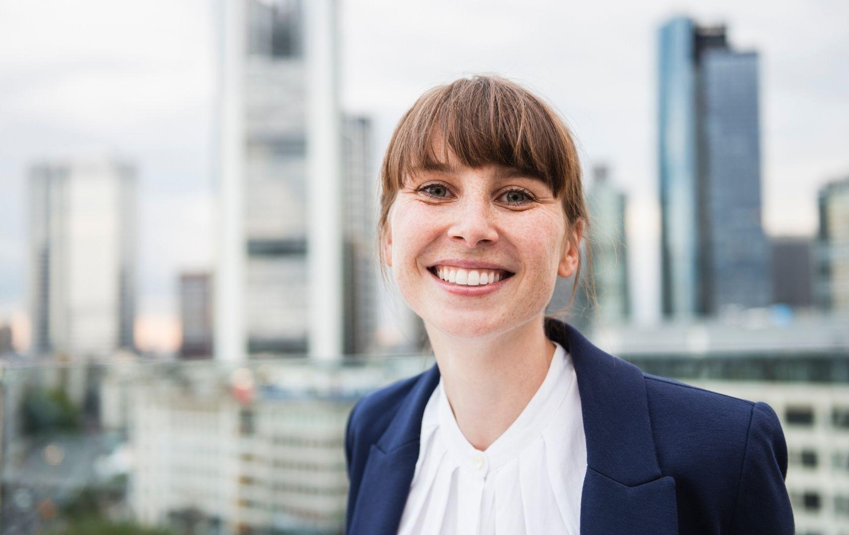 Junge Businessfrau lachend vor Frankfurter Skyline