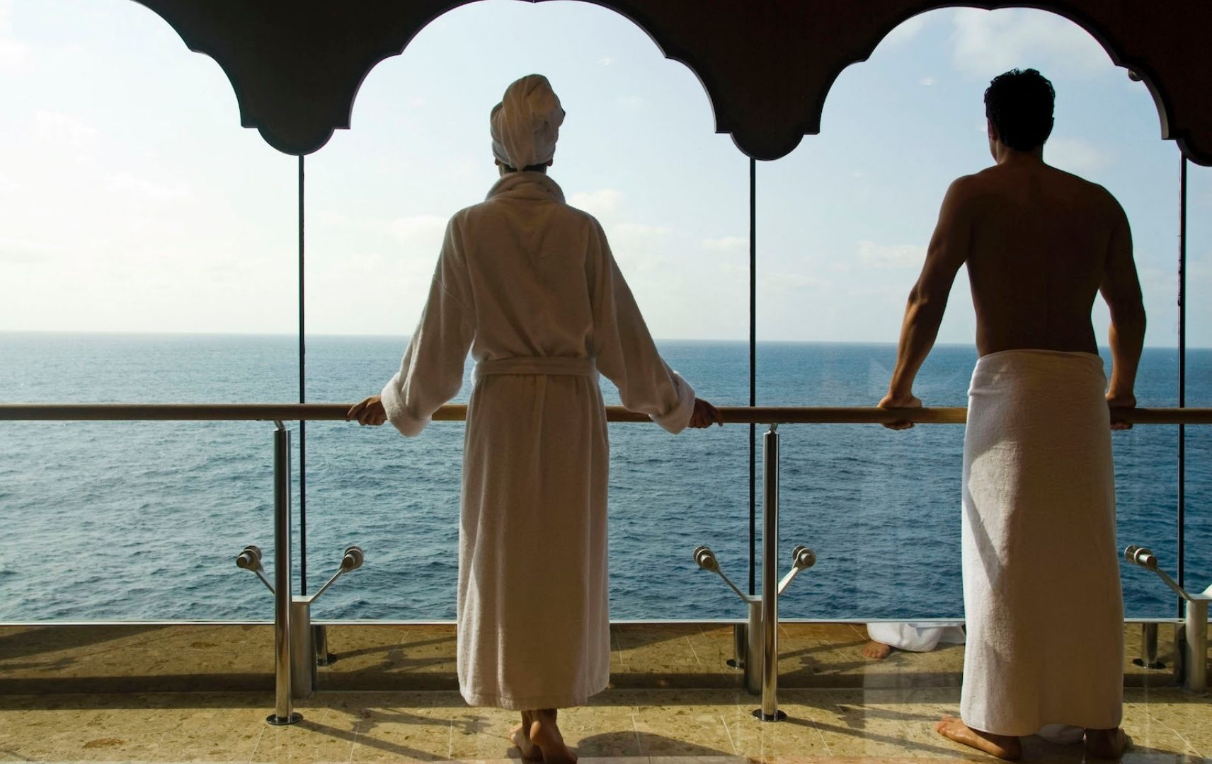 Mann und Frau mit Bademänteln schauen auf das Meer