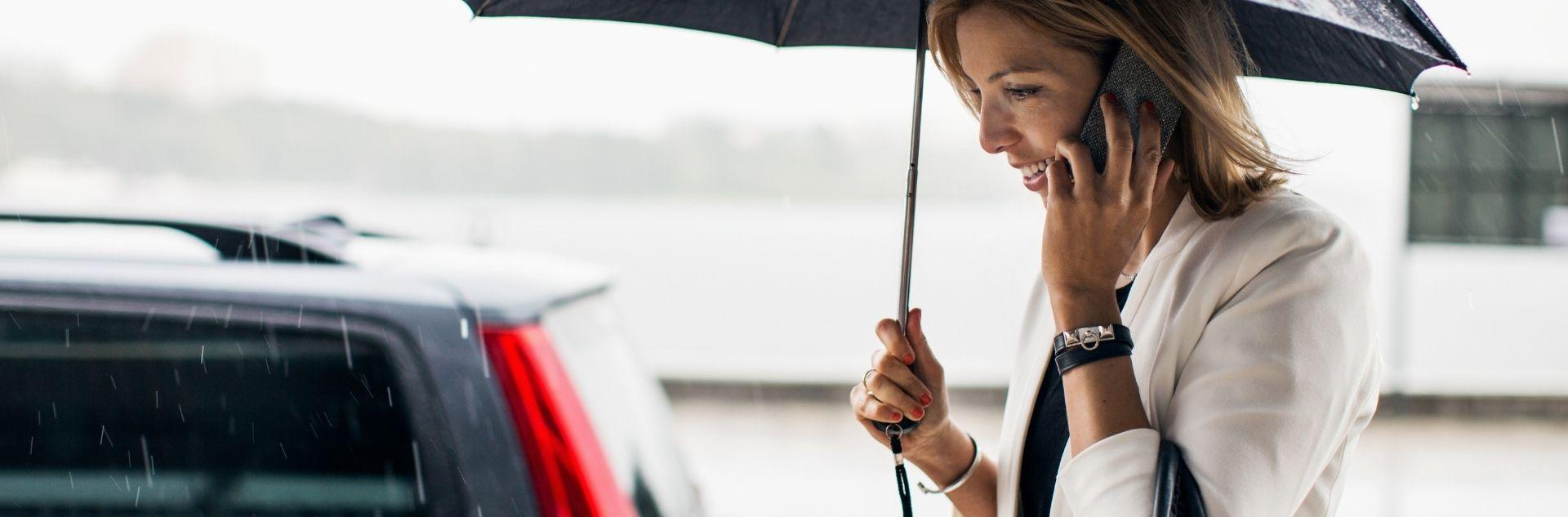 LCC Security Management Frau mit Regenschirm telefoniert