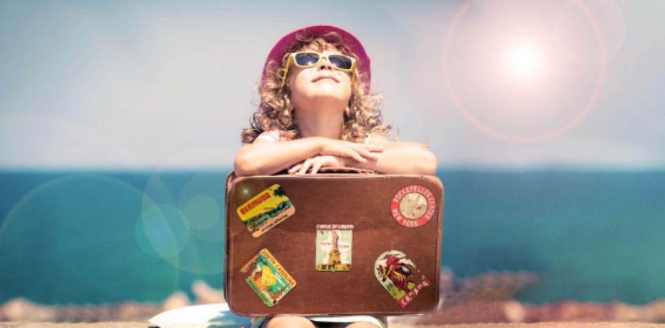 Kind sitzt mit Koffer und schaut in die Sonne
