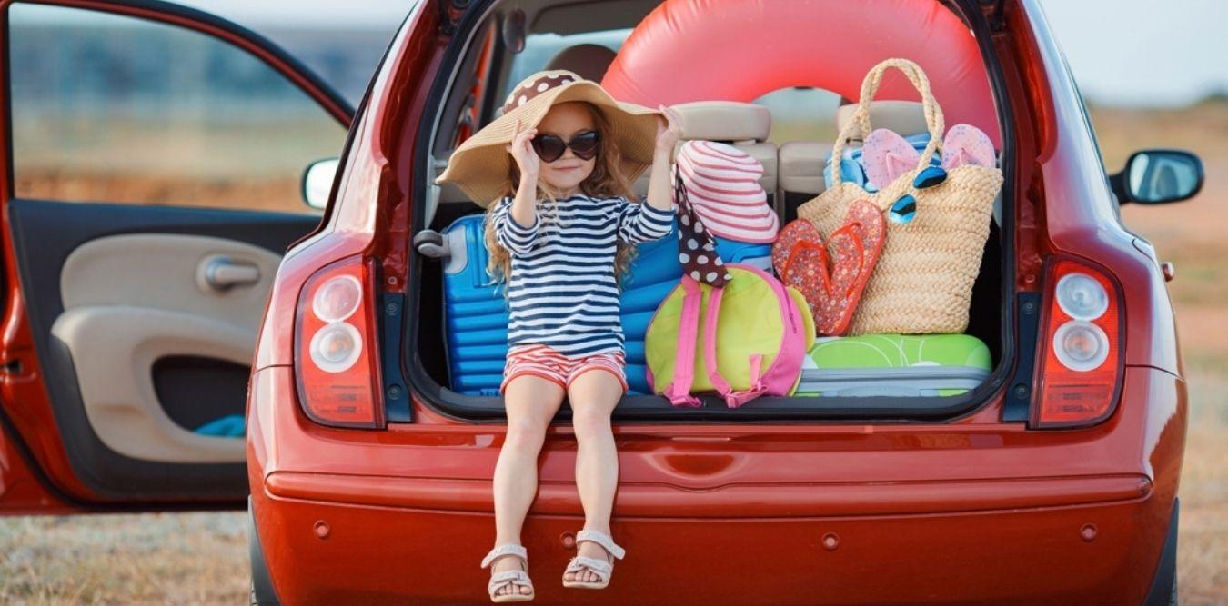 Kleines Mädchen und Auto mit Gepäck