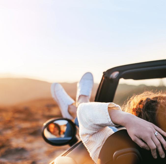 Frau streckt Beine aus dem Auto