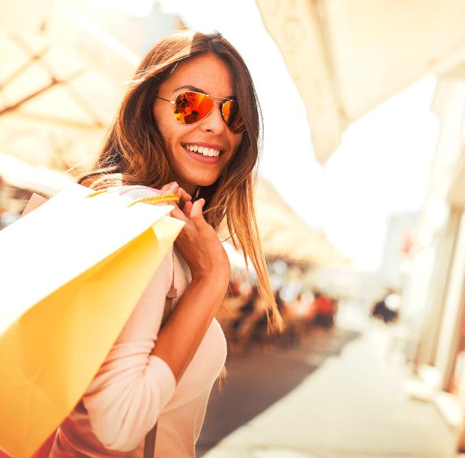 Frau mit Einkaufstüte und Sonnenbrille