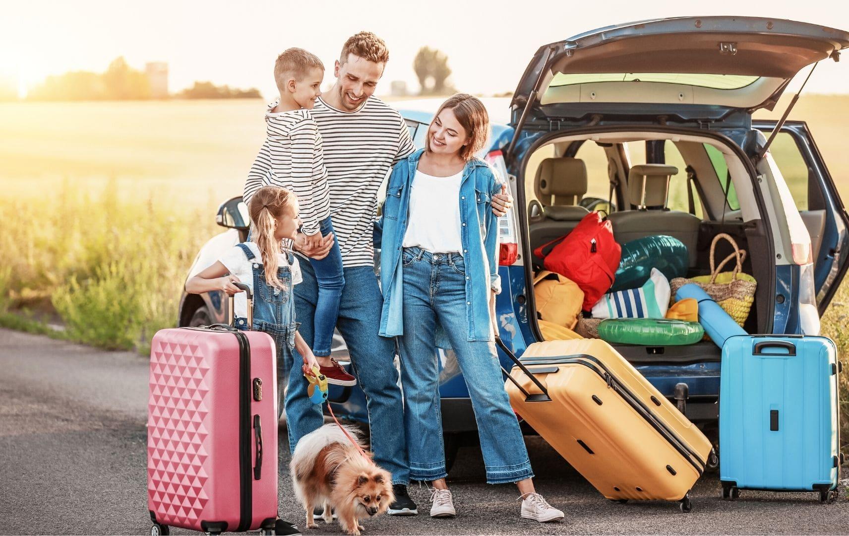 Familie mit Hund und gepackten Koffer Gepäck im Kofferraum