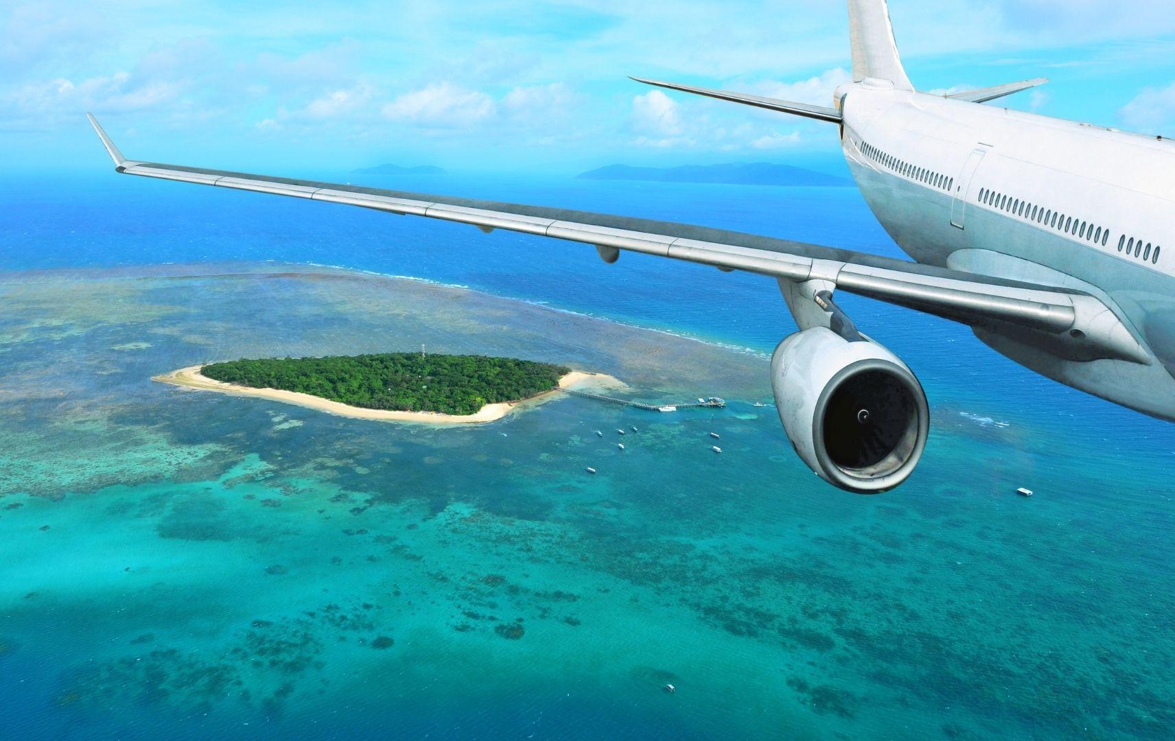 Flugzeug fliegt über Meer und Insel