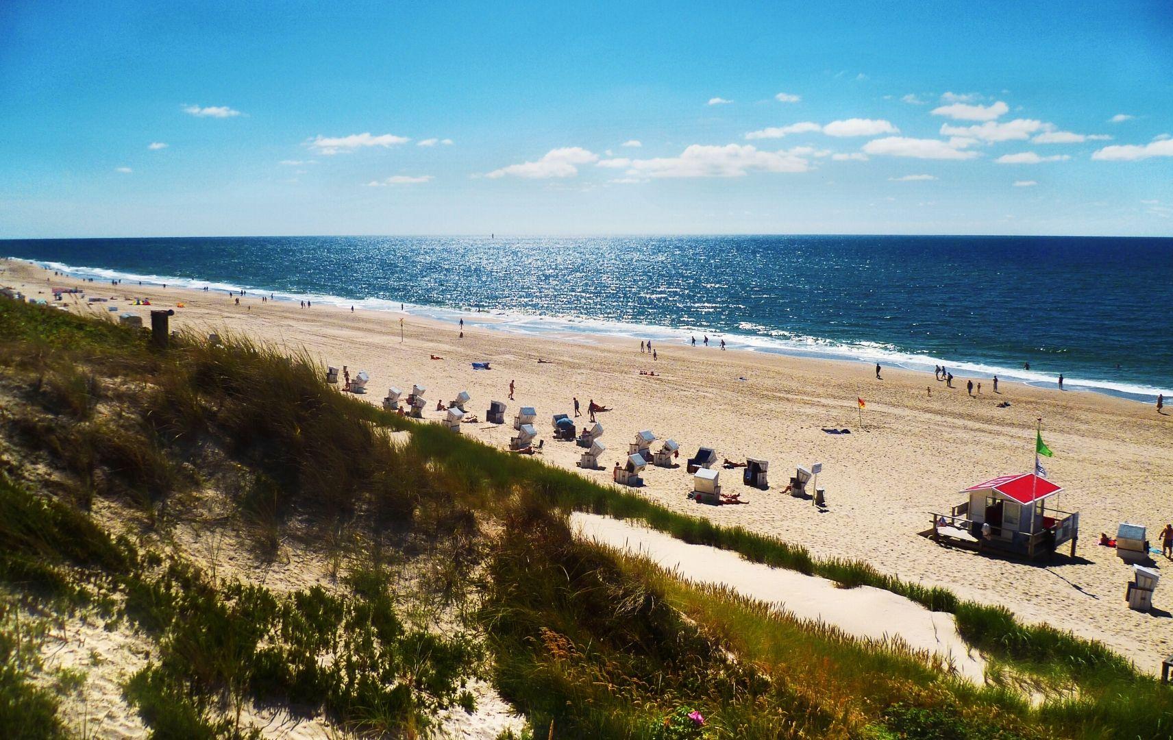 Strandkörbe und Urlauber an der Küste