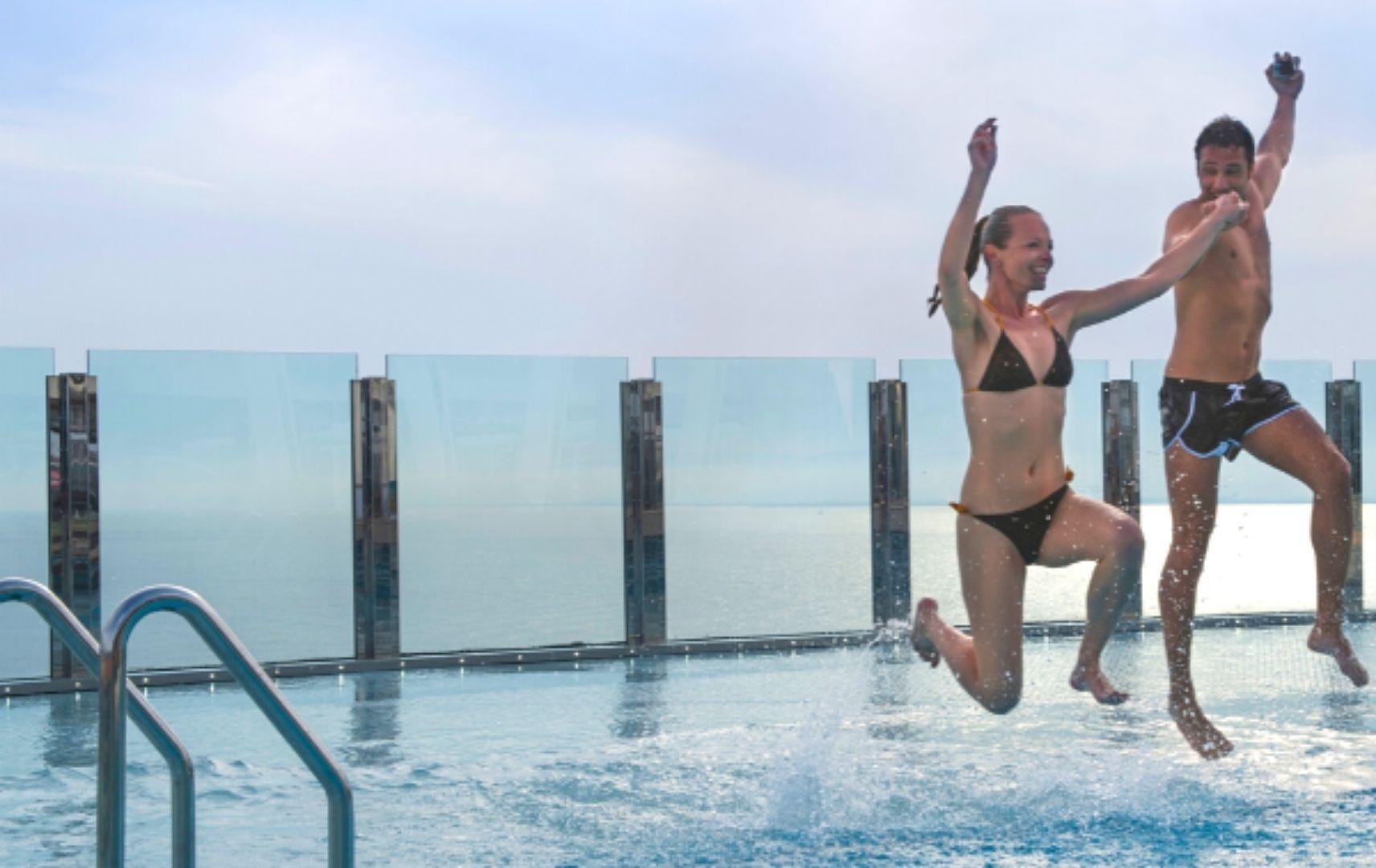 Mann und Frau springen in den Pool