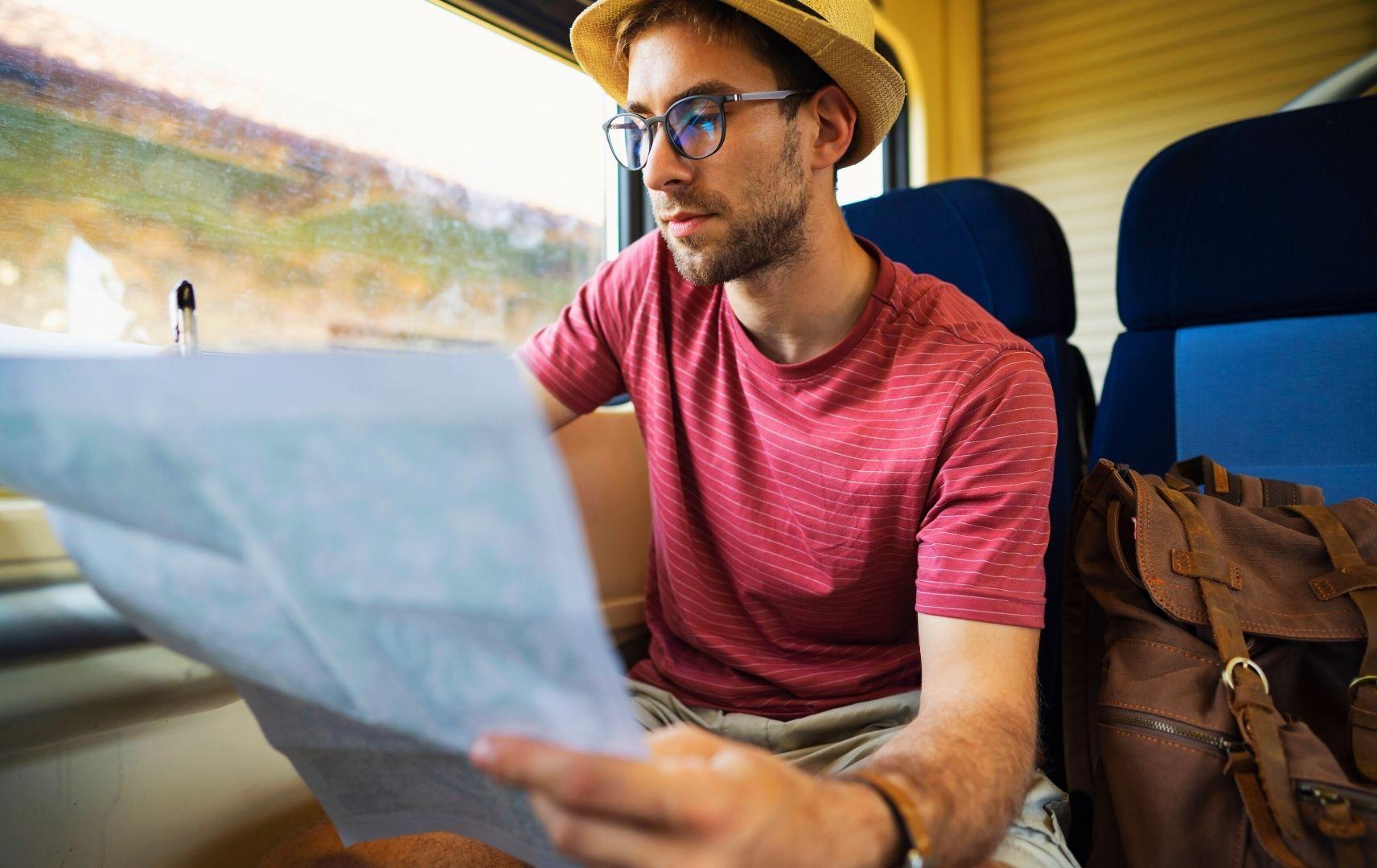 Man sitzt mit Karte in der Hand im Zug
