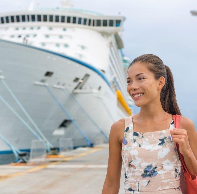Frau mit Handtasche lächelt im Hintergrund Kreuzfahrtschiff