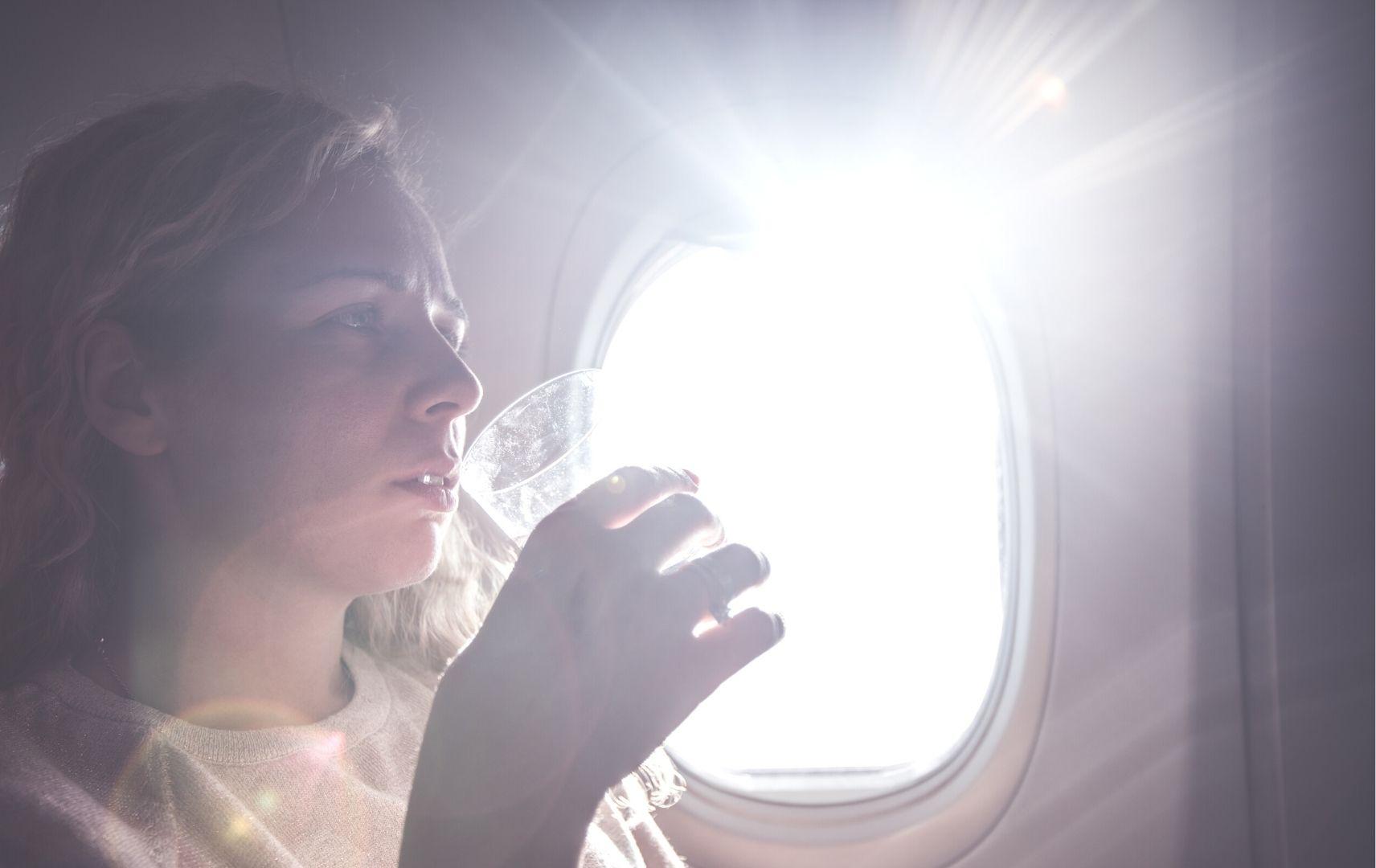 trinkende Frau im Flugzeug