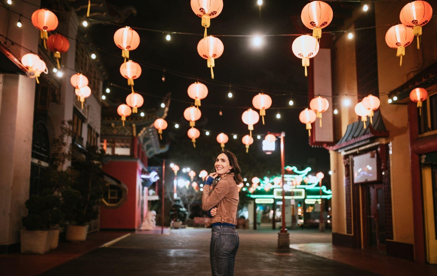 Frau in Singapur bei Nacht mit Lampinons