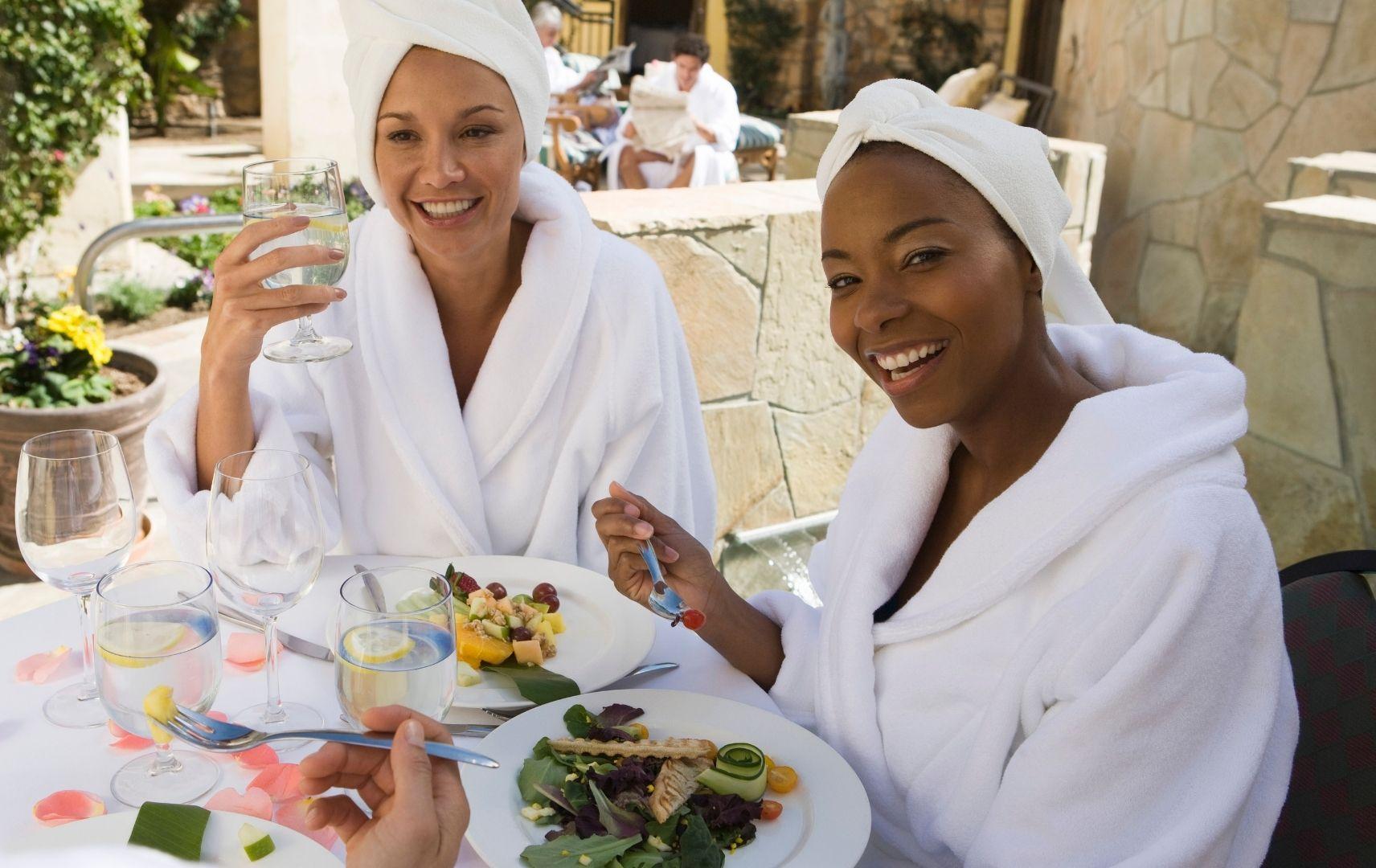 Zwei Frauen mit Bademäntel Frühstücken draußen
