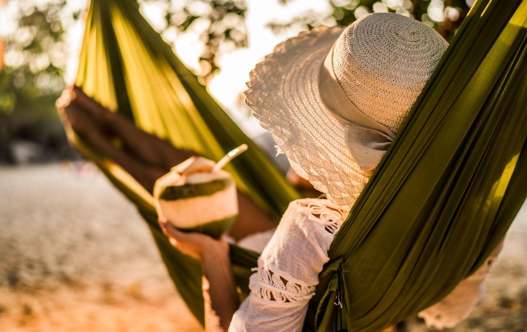 Frau mit Hut und Kokosnuss in der Hand in Hängematte