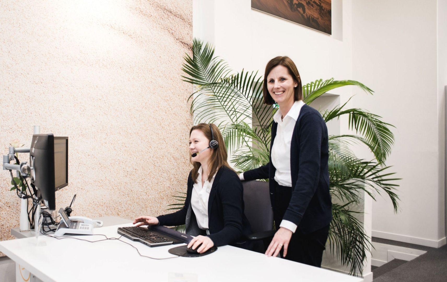 Zwei Frauen am Bürotisch Computer Headset