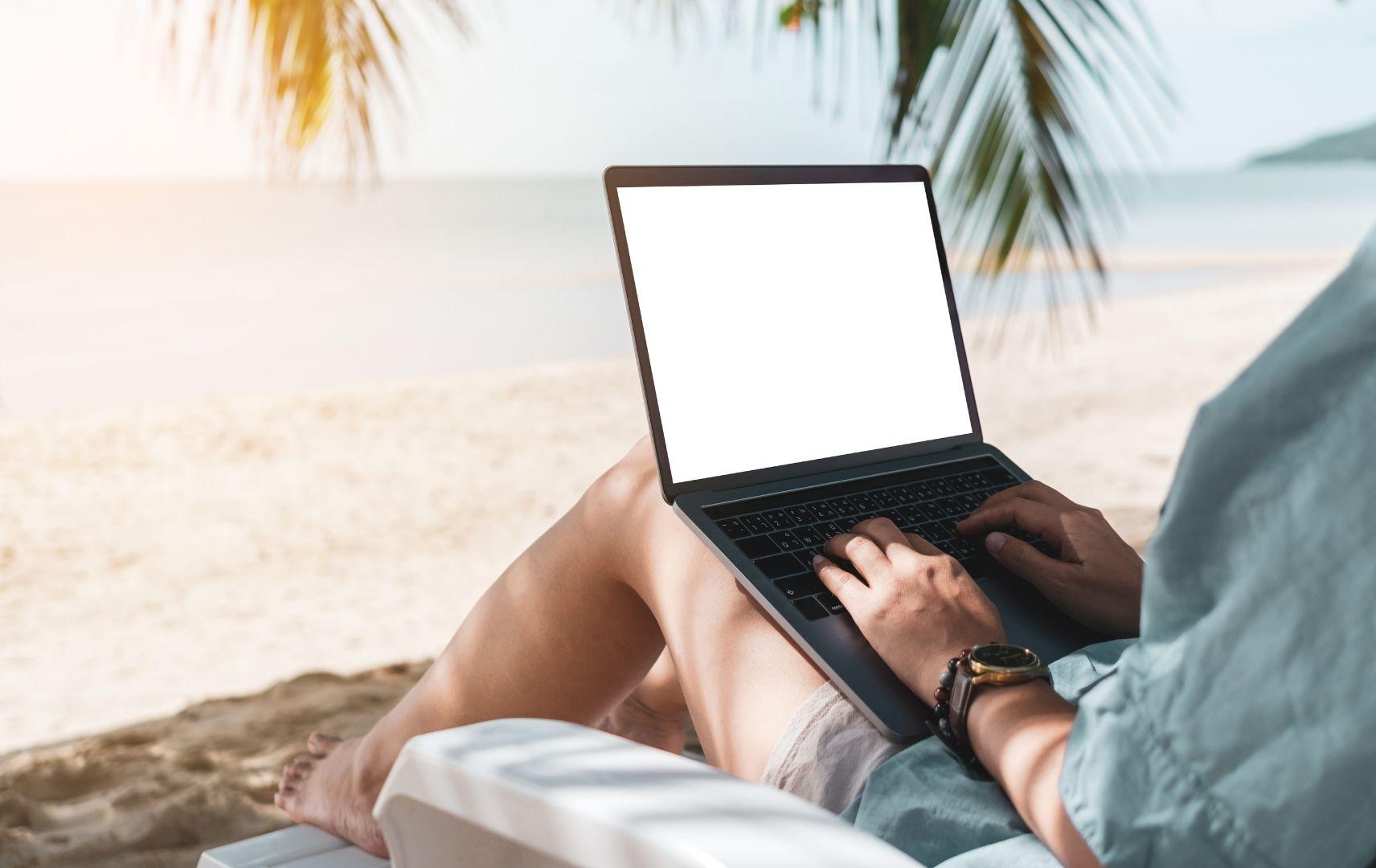 Bleisure Travel Frau am Strand mit Laptop