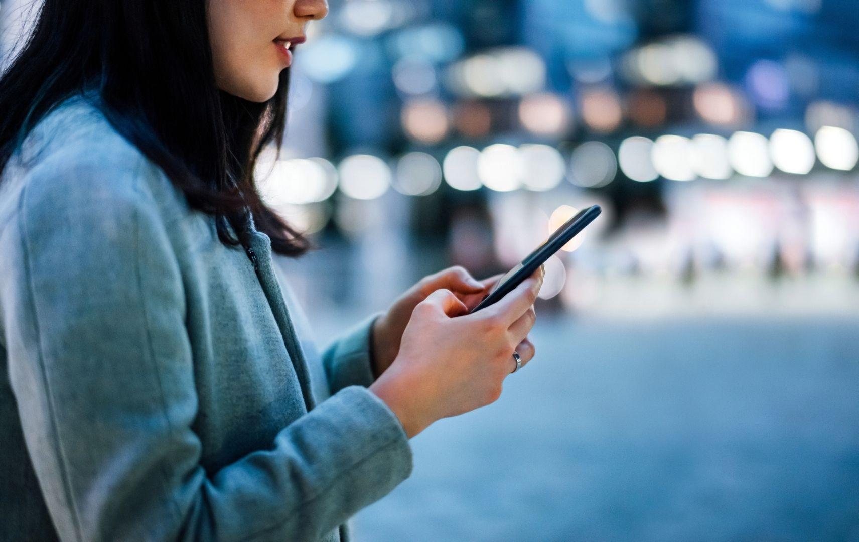 Mit LCC Bridge-IT das beste Angebot buchen - Geschäftsfrau mit Smartphone