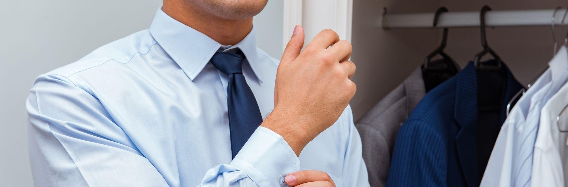 Dresscode Guide Mann knöpft Ärmel von seinem Businesshemd zu