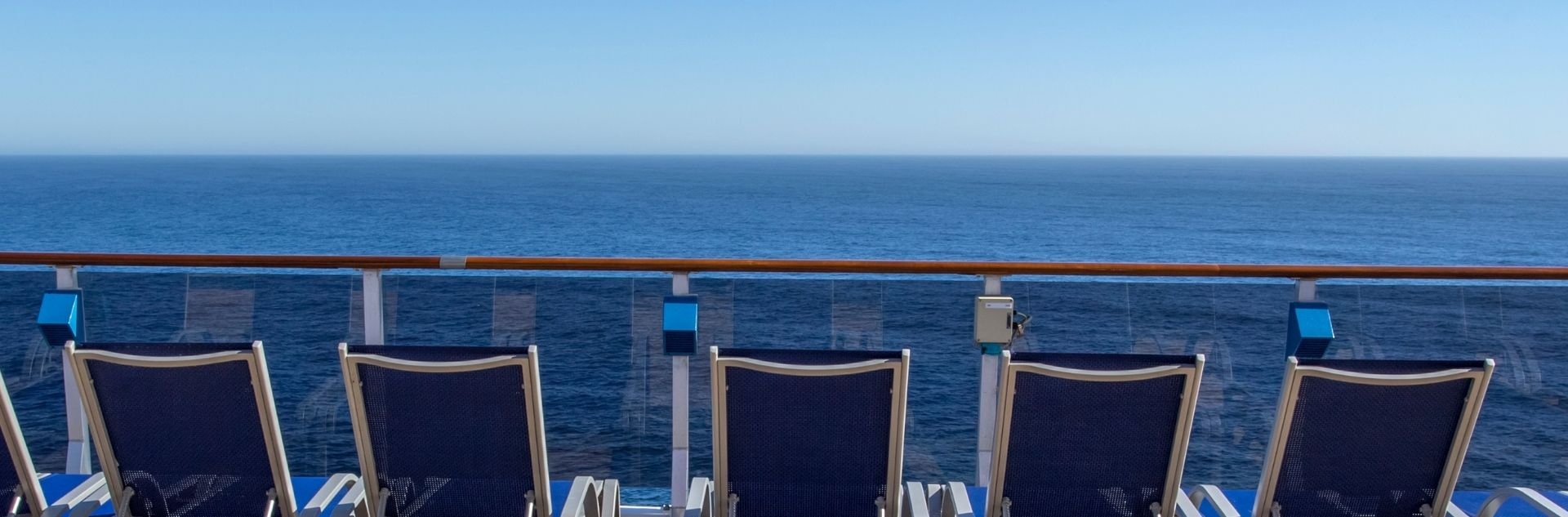 Liegestühle auf dem Kreuzfahrtdeck mit Ausblick auf das Meer