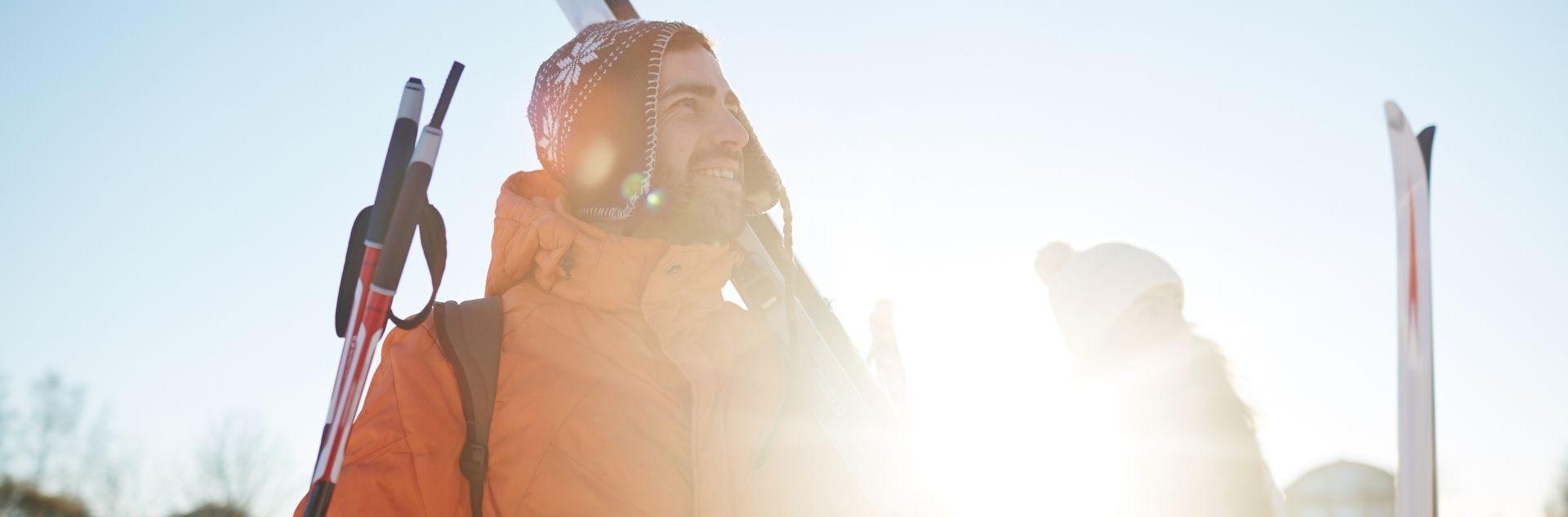 Mann und Frau mit Mütze und Skiern