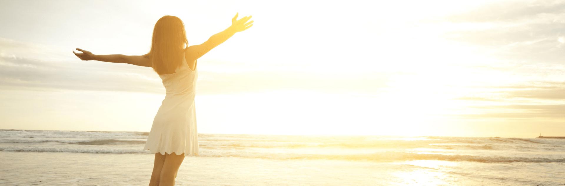 Frau mit offenen Armen am Strand