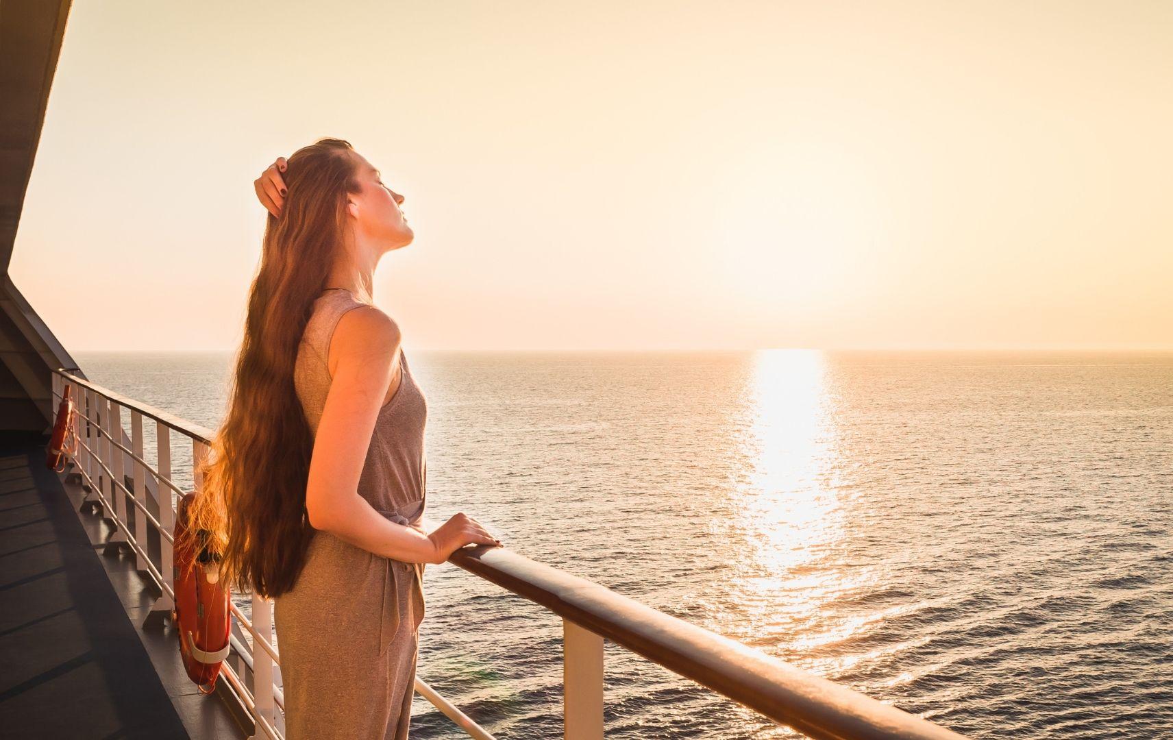 Frau auf Kreuzfahrtschiff an Reling
