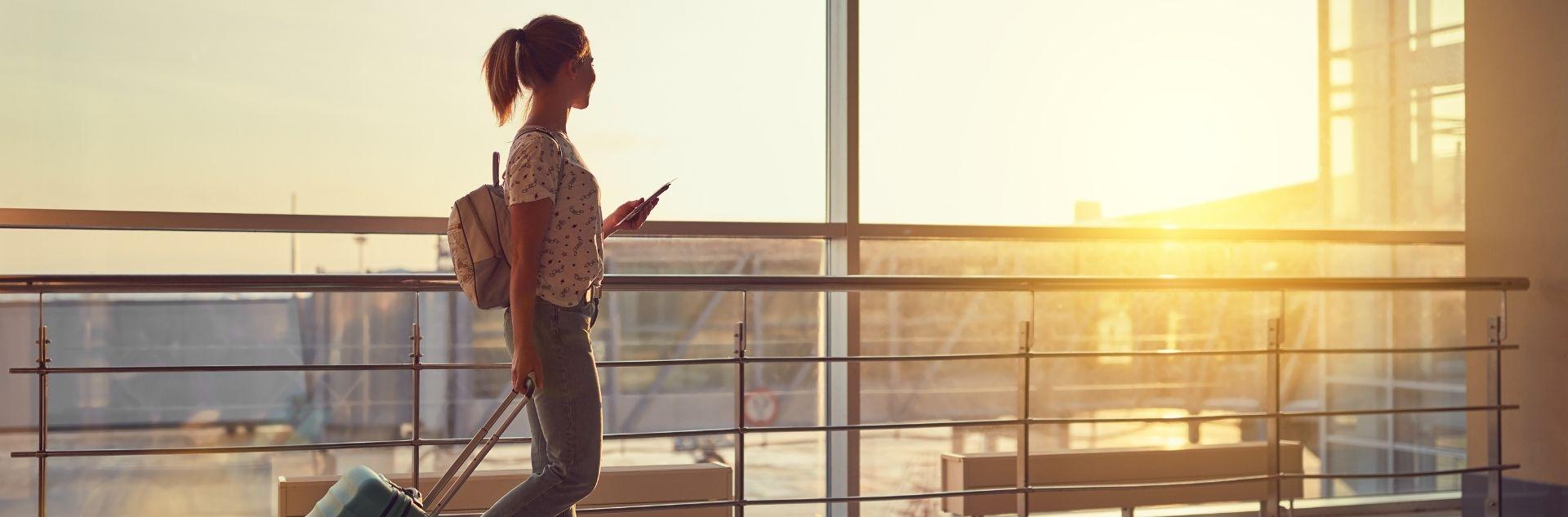 Frau am Flughafen mit Koffer, Sonnenuntergang