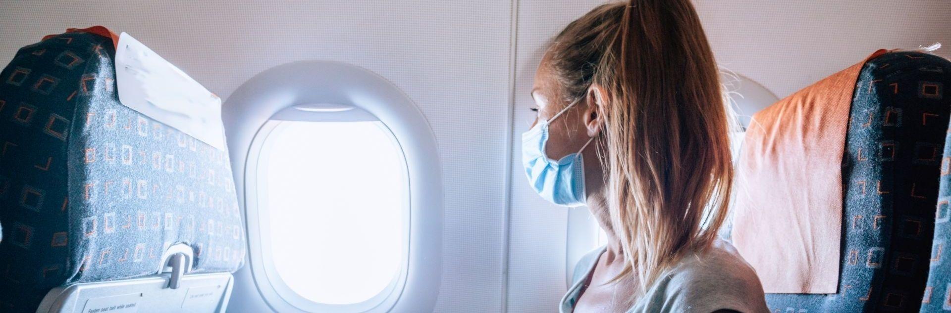 Frau mit Maske im Flugzeug