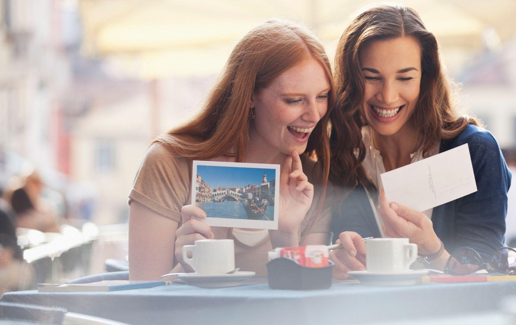 Frauen mit Postkarte im Cafe, Postando
