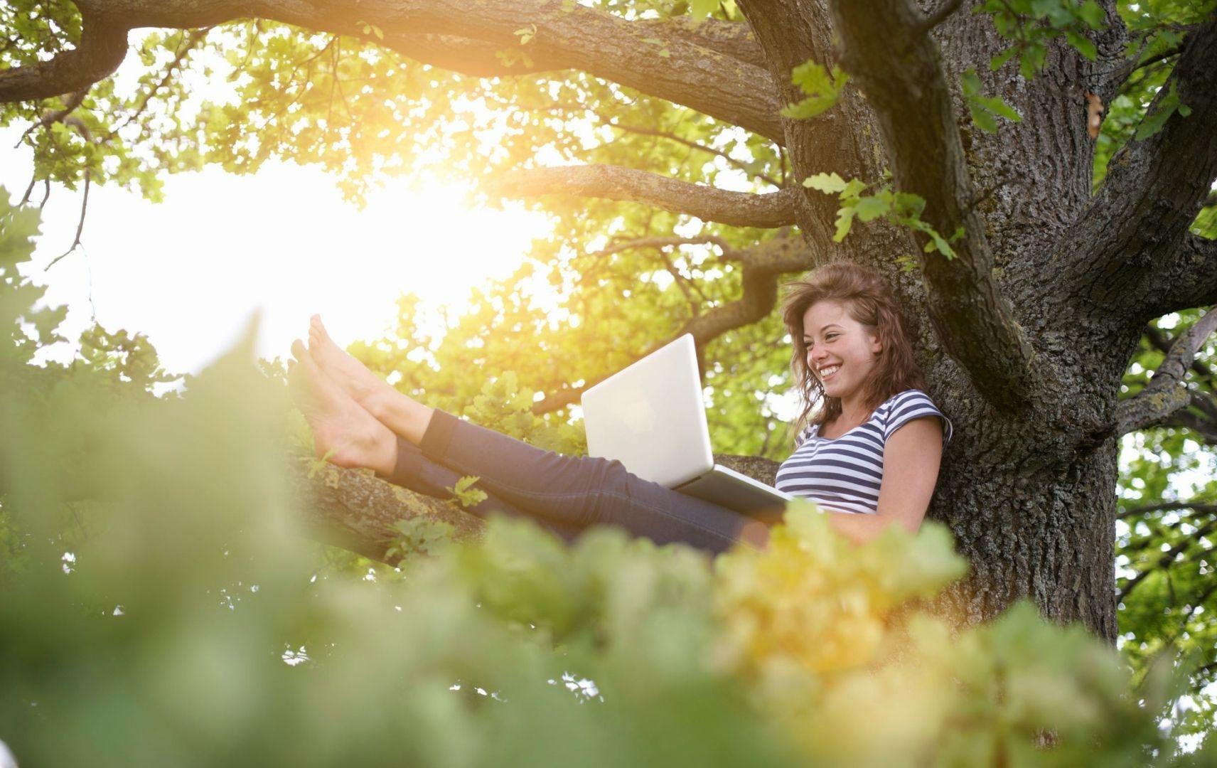 Nachhaltig Reisen Geschäftsreisebüros helfen - junge Frau mit Laptop im Grünen