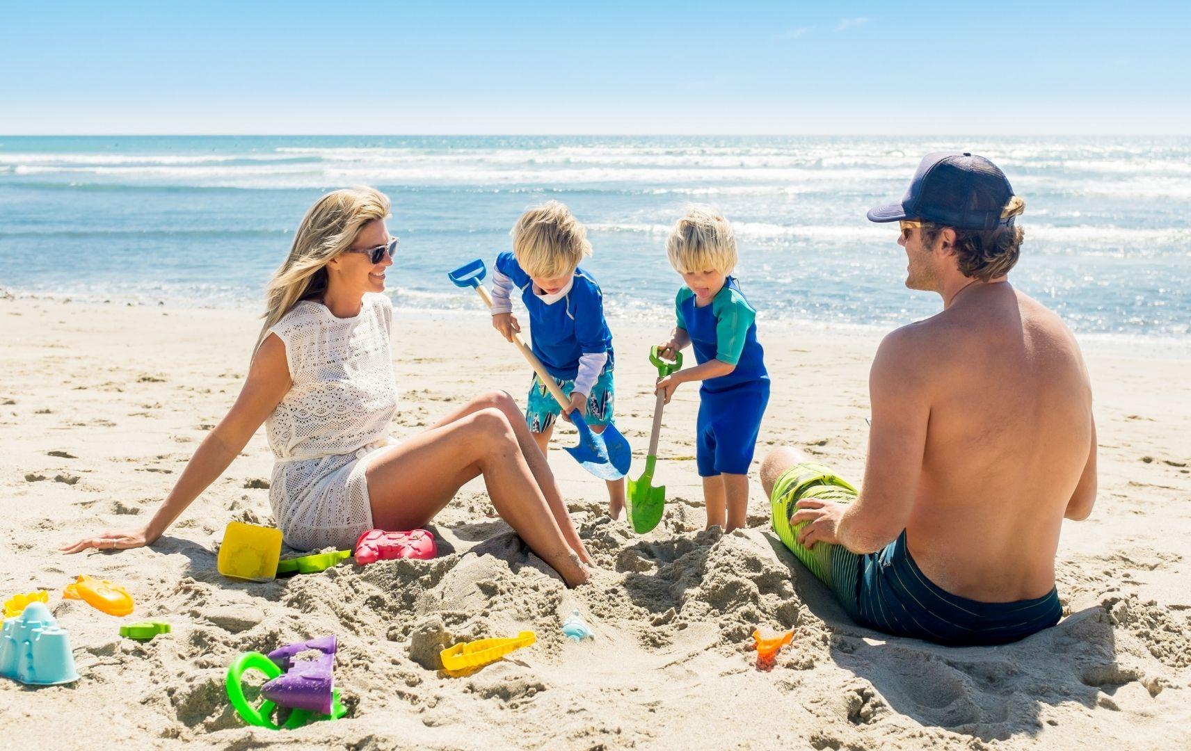 Strandspiel - Eltern spielen mit Kindern im Sand