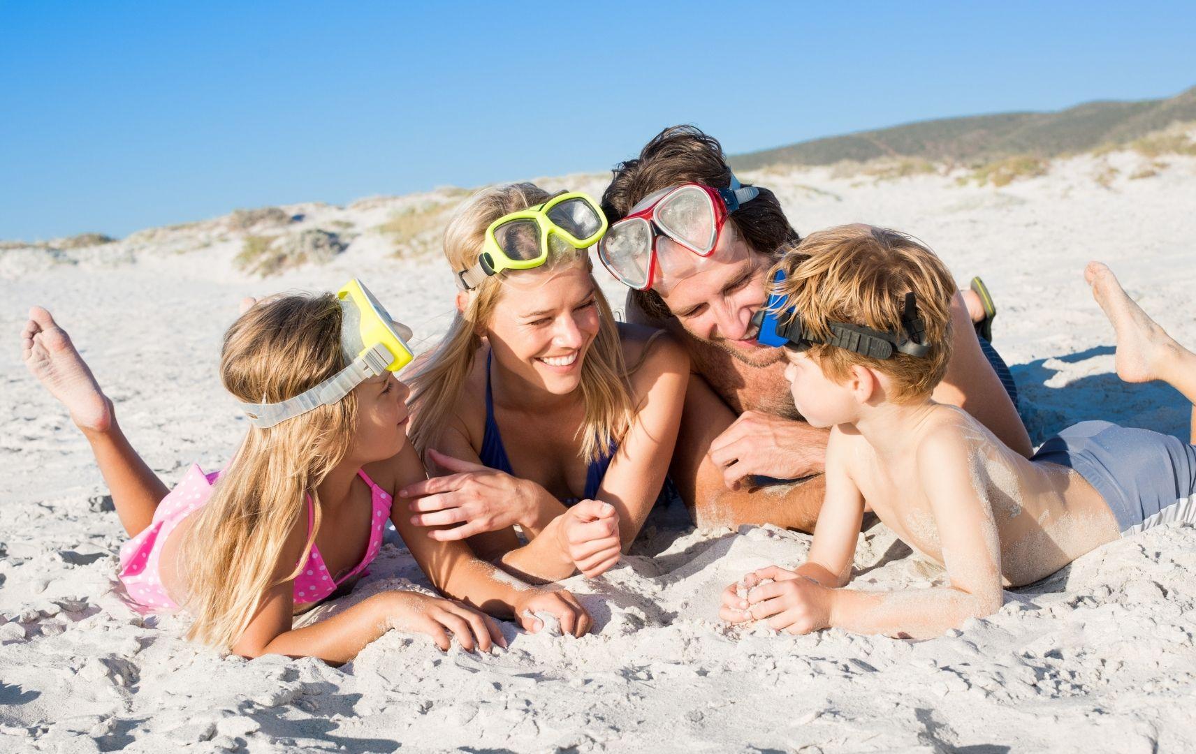 Strandspiel - Familie liegt im Sand