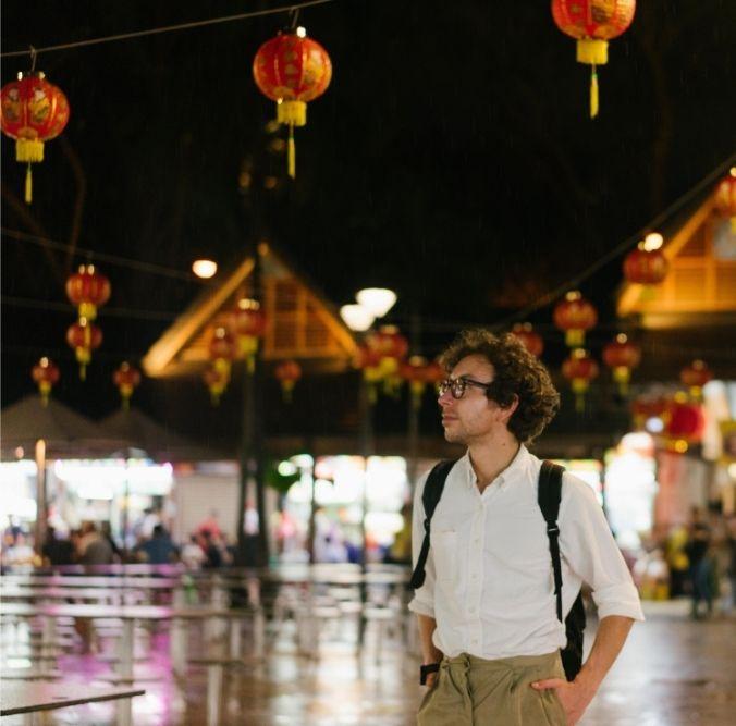 Mann mit Rucksack in Singapur bei Nacht