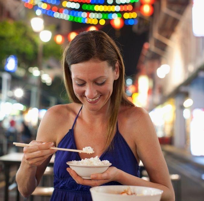 Foodie, Frau in Singapur mit Reisschüssel am Essen