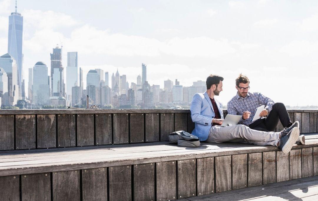 Geschäftsreisen endlich einfach - zwei junge Männer entspannt vor der Skyline von New York