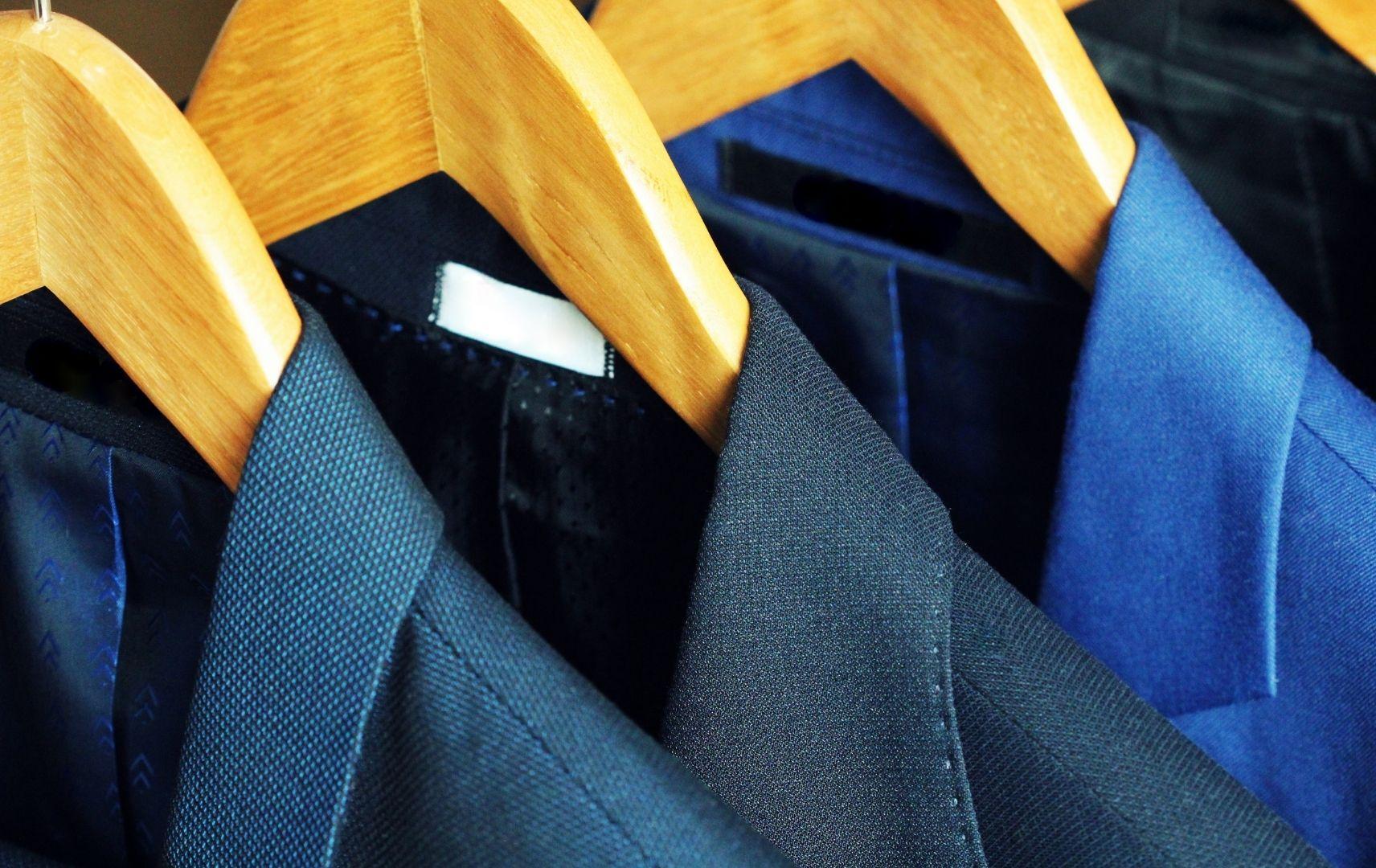 Anzüge auf Bügeln im Kleiderschrank