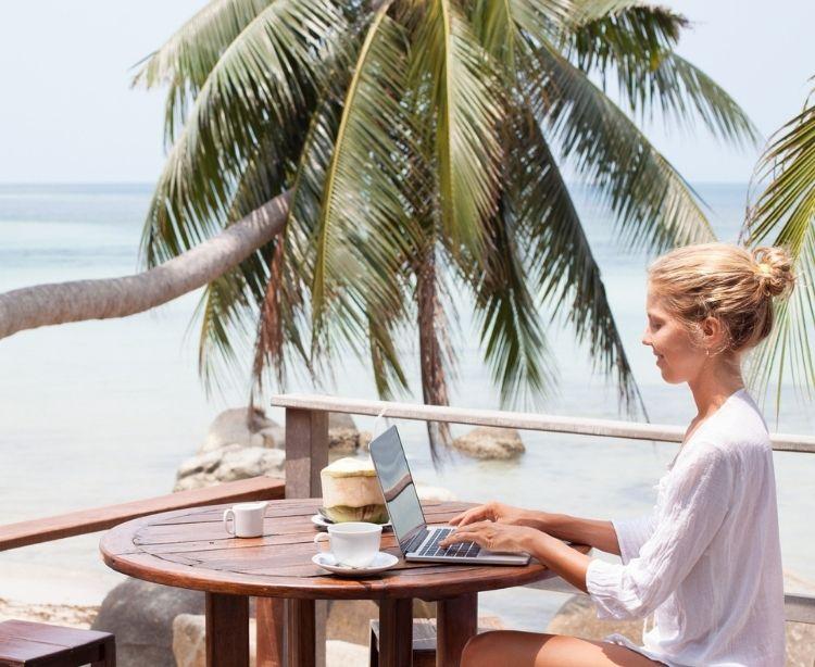 Frau sitzt auf einer Terrasse am Strand mit Palmen und arbeitet an ihrem Laptop