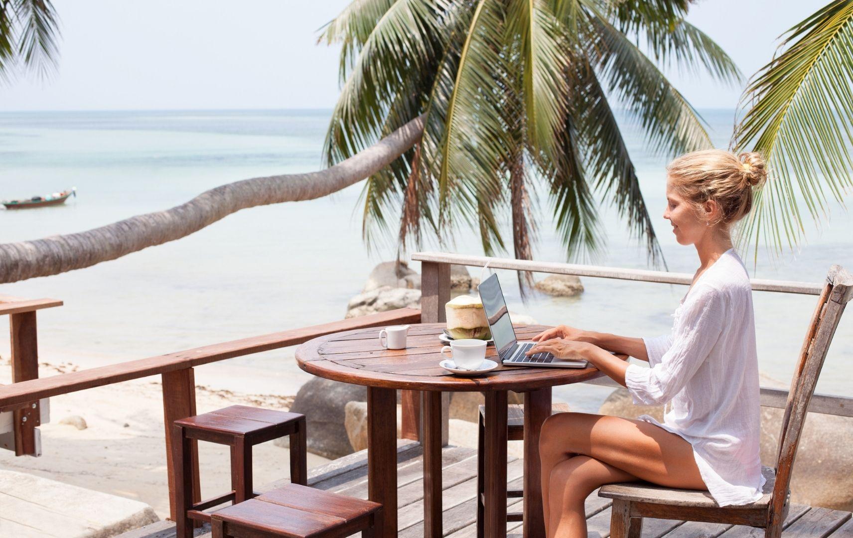 Frau sitzt auf Terrasse am Palmenstrand und arbeitet am Laptop
